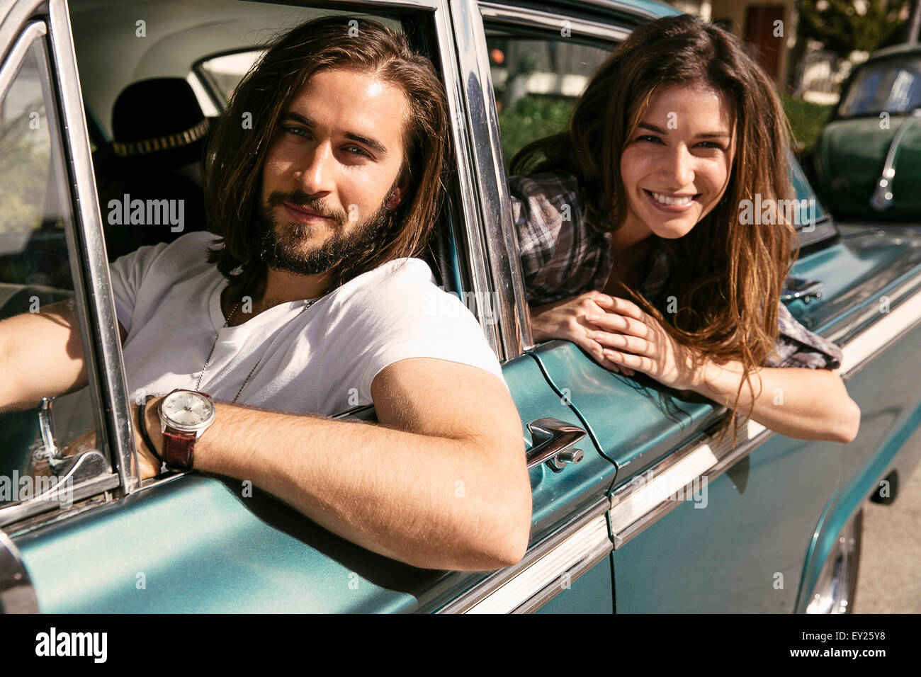 Young couple leaning out of vintage car windows - Stock Image