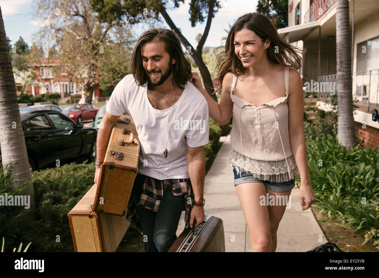 Young couple struggling to carry suitcases for road trip - Stock Image