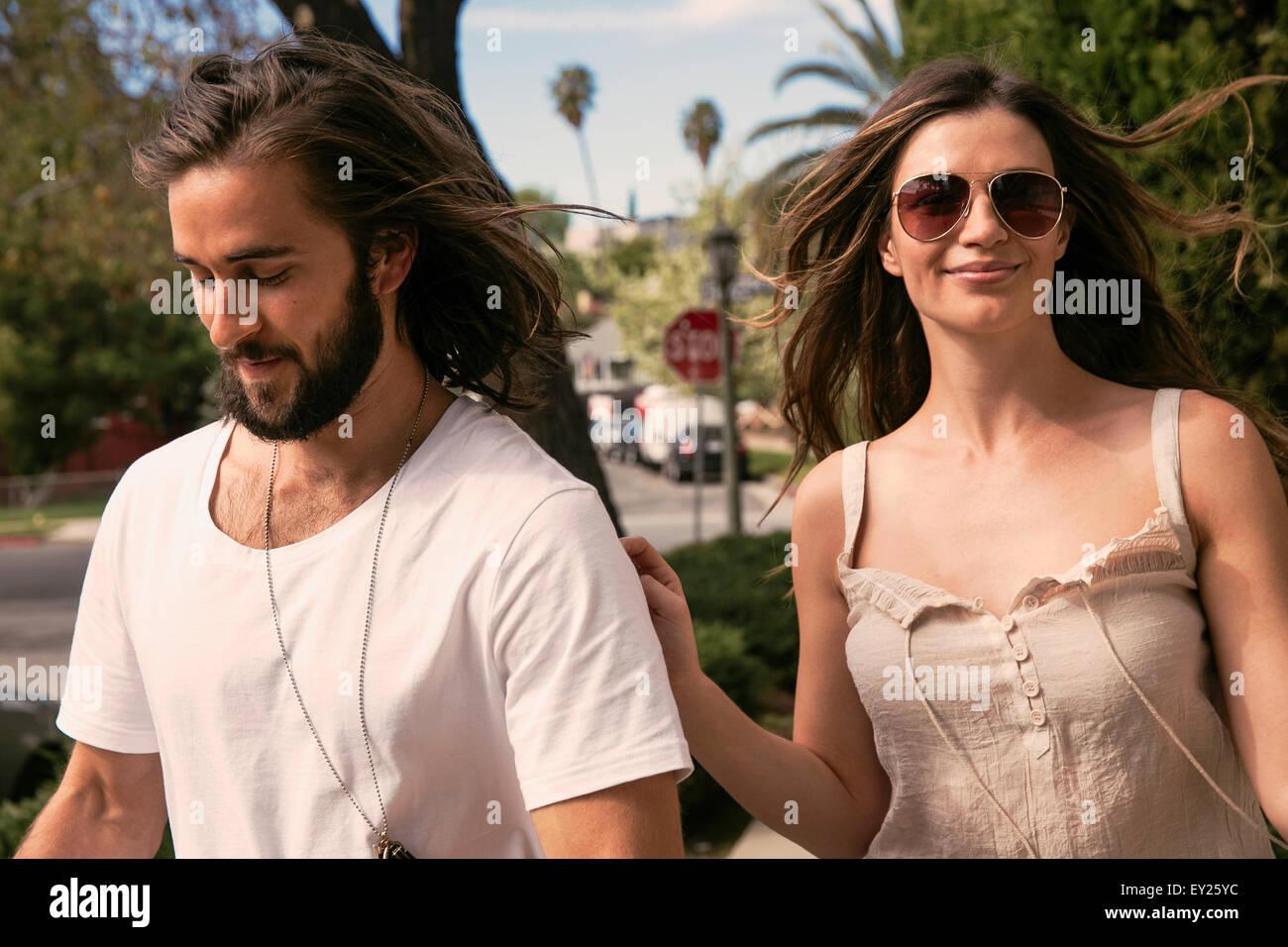 Young couple walking along street - Stock Image