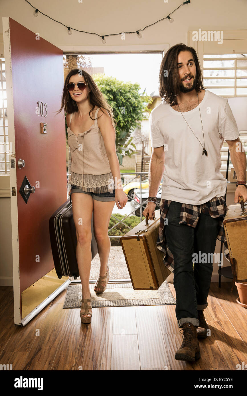 Young couple carrying suitcases through front door - Stock Image
