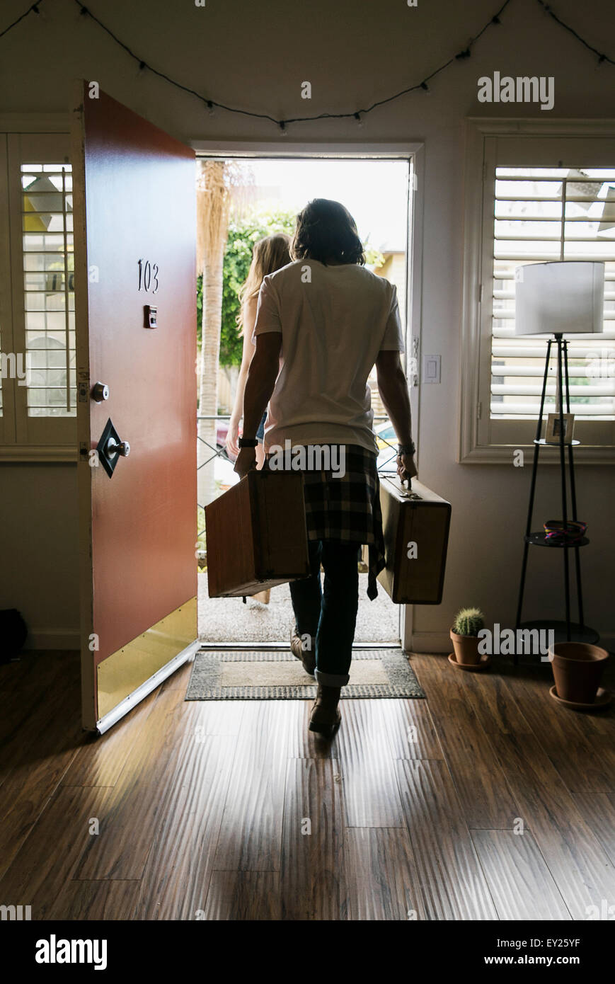 Rear view of young couple carrying suitcases out of front door - Stock Image