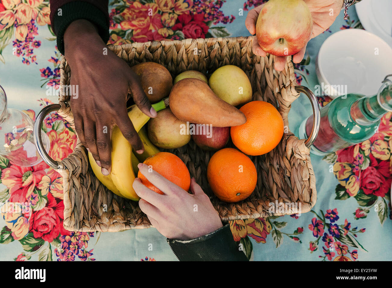 Three adult hands selecting fruit form basket - Stock Image