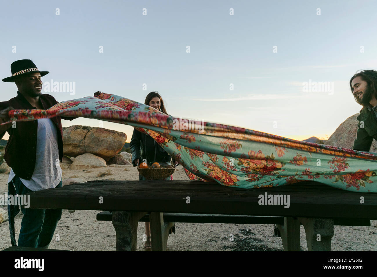 Three Adult Friends Preparing Picnic Table Cloth In Desert Los - Picnic table los angeles