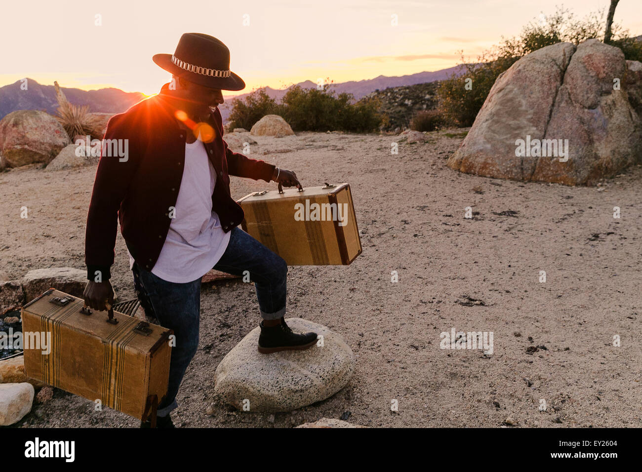 Mid adult man unloading road trip suitcases at sunset, Los Angeles, California, USA - Stock Image