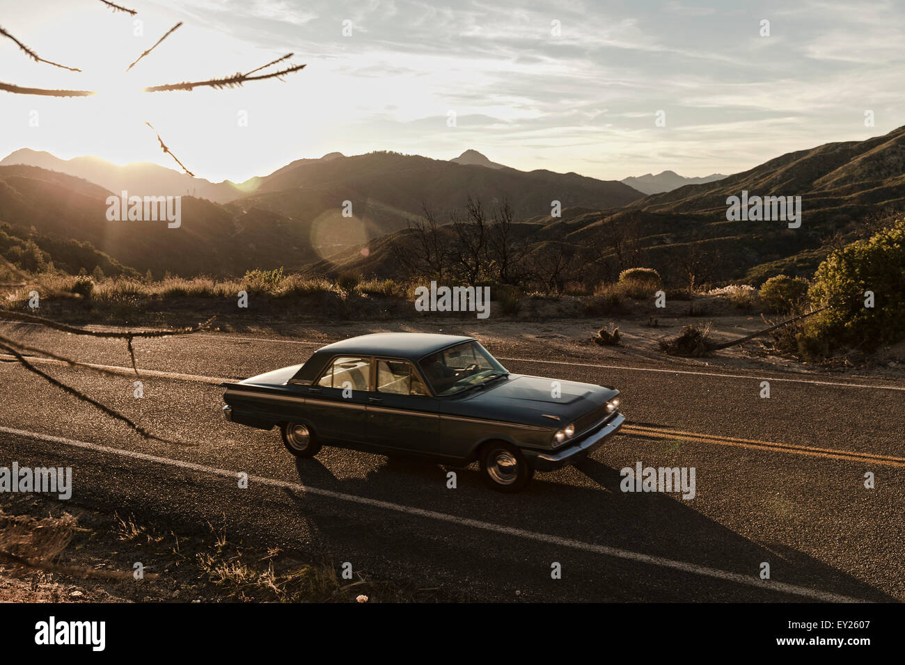Young man driving vintage car on road trip in desert, Los Angeles, California, USA Stock Photo