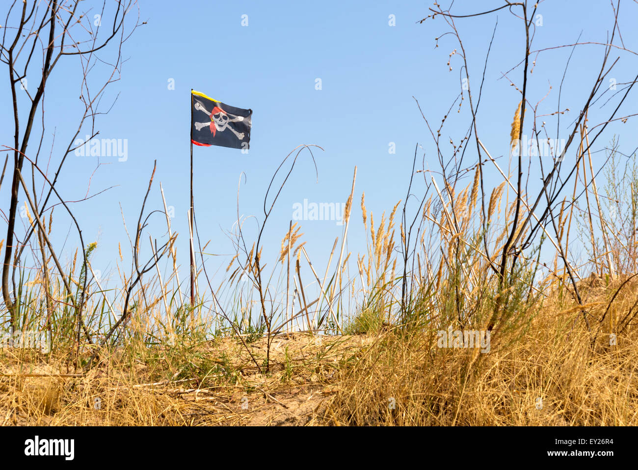 The black Jolly Roger pirate flag flutters in the wind over the hill - Stock Image