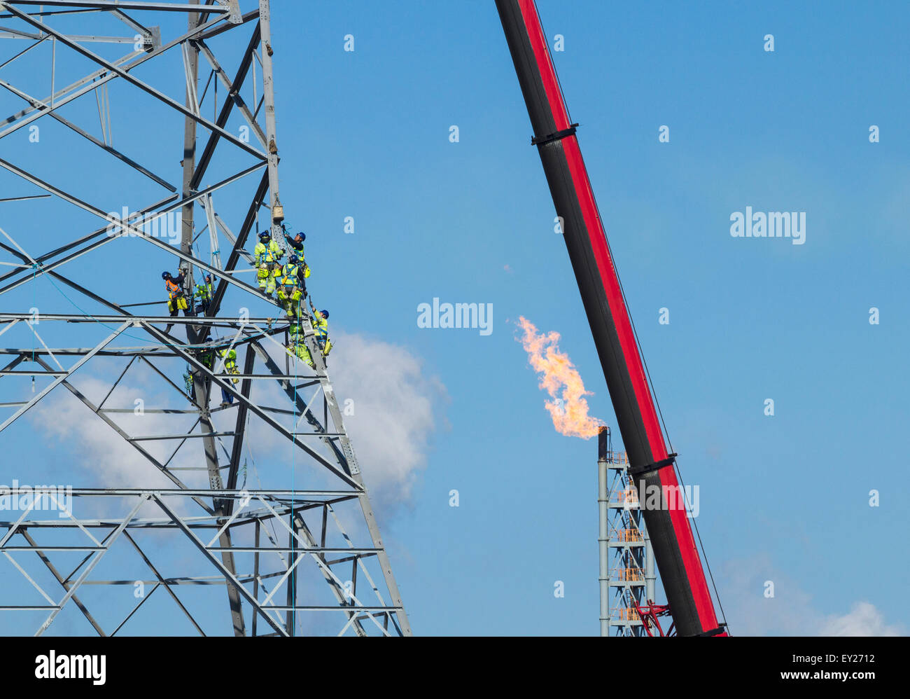 Workers erecting 145 metre tall electricity pylons across the river Tees near Middlesbrough, north east England, - Stock Image