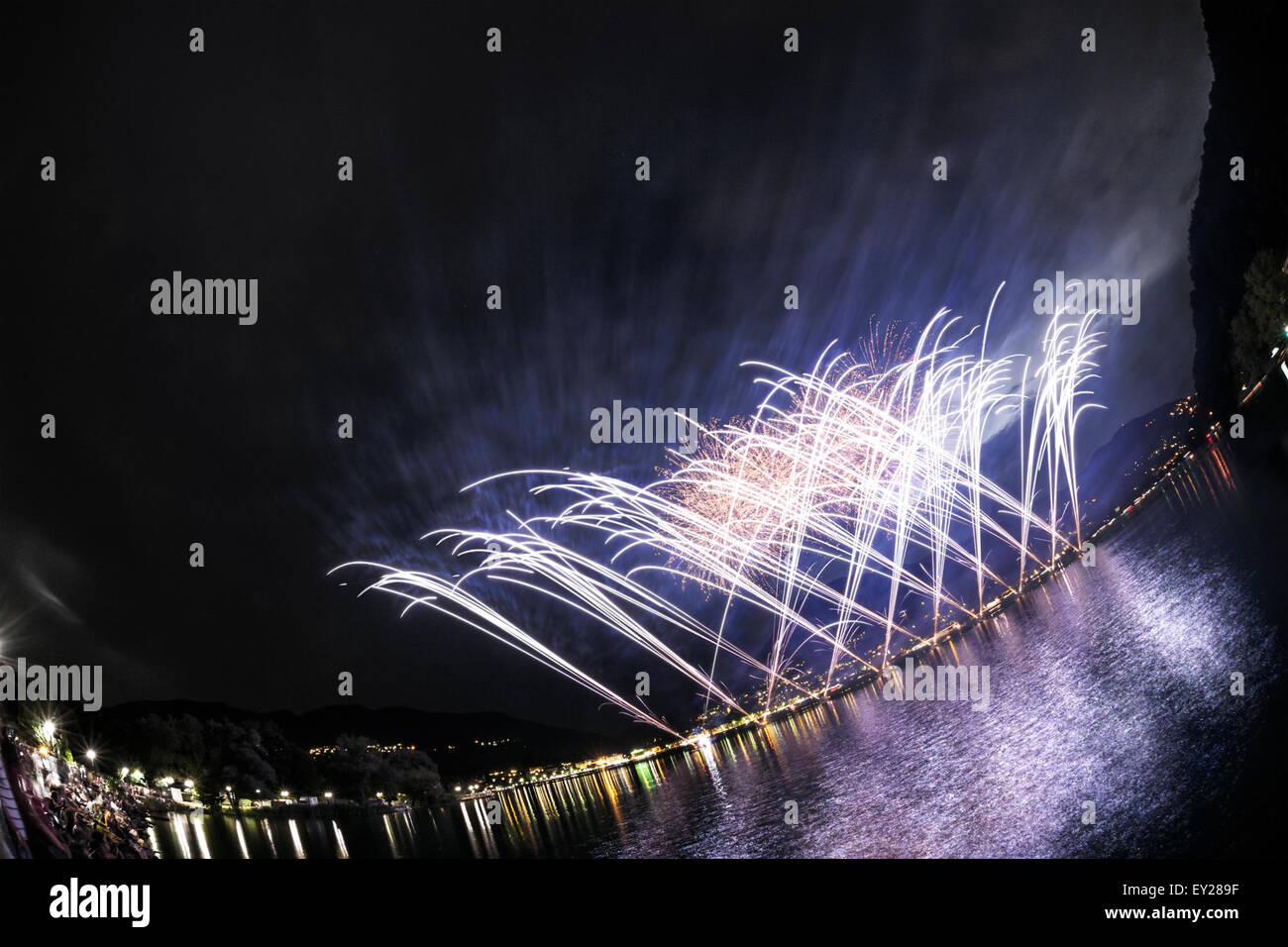 Fireworks on the Lugano Lake in a summer evening seen from lakefornt of Lavena-Ponte Tresa, Lombardy - Italy Stock Photo