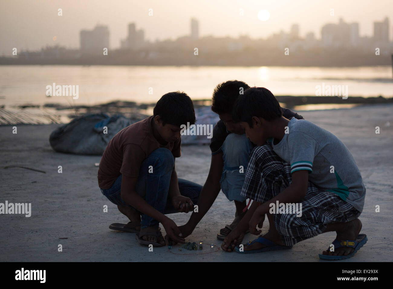 Indian kids playing marbles near the beach during sunset in Mumbai, India. - Stock Image