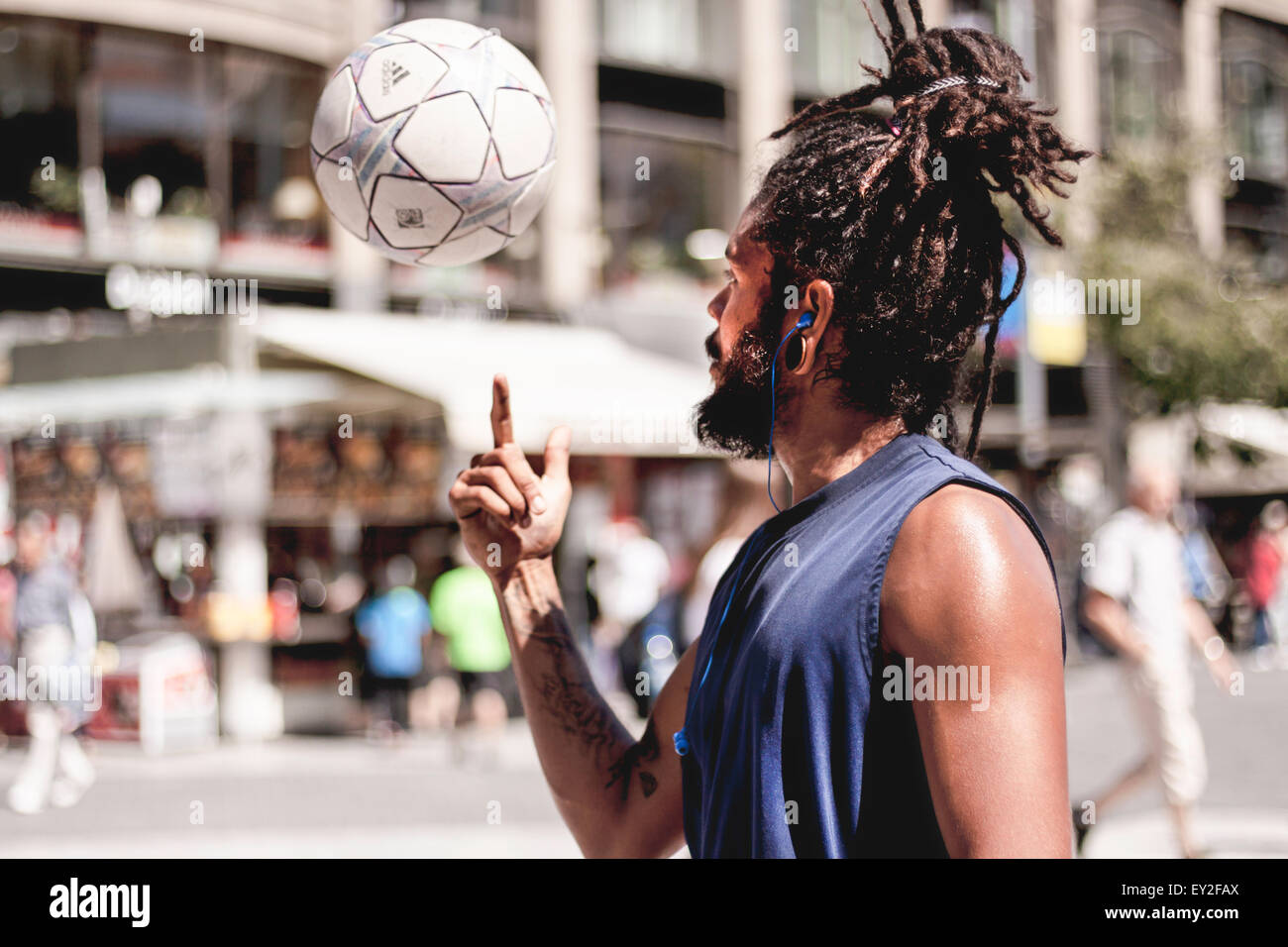 Young man doing balance tricks with his white and blue football in the center of Prague. Stock Photo
