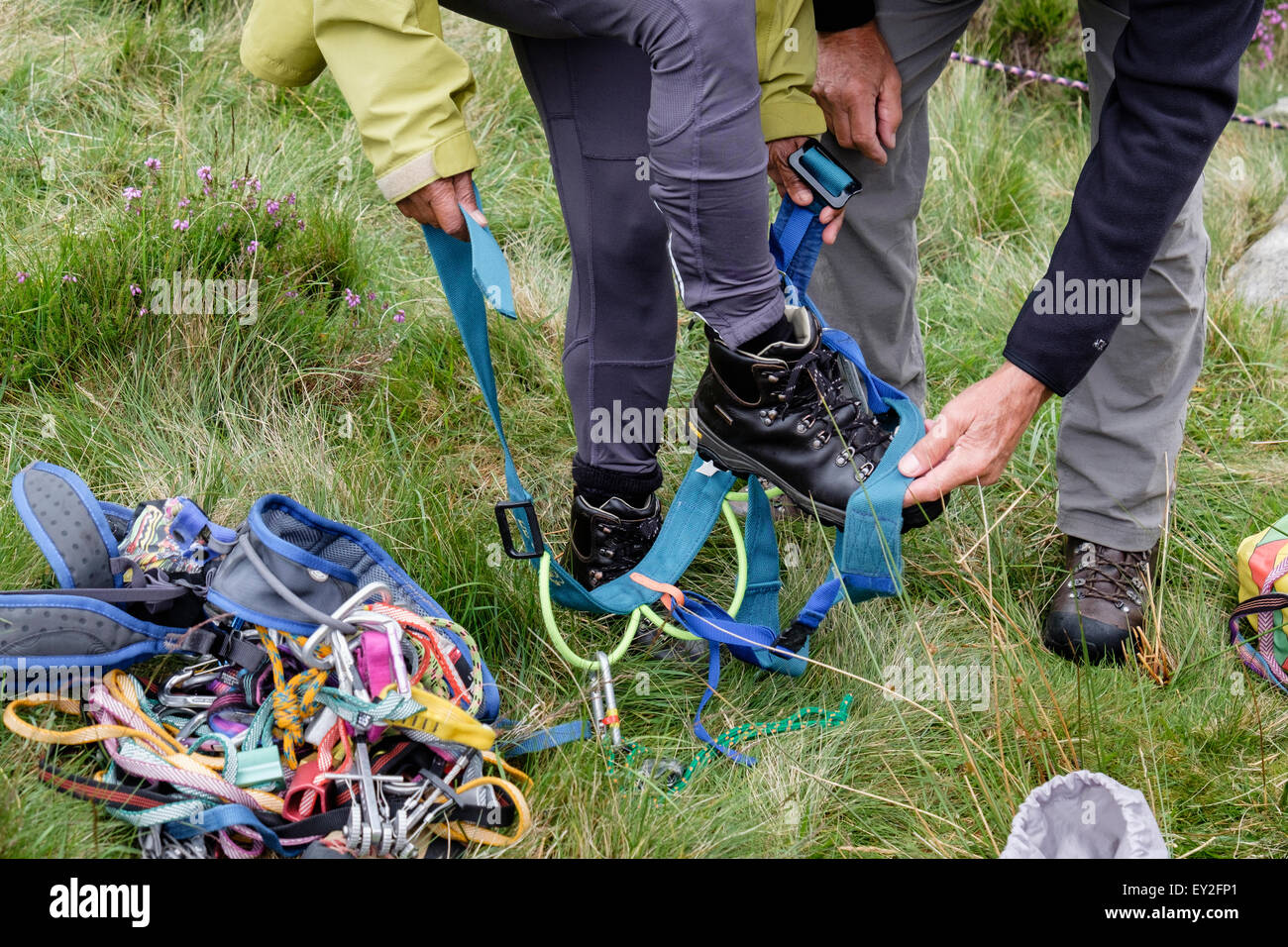 Rock climber teaching a novice to put on a climbing harness. UK, Britain - Stock Image