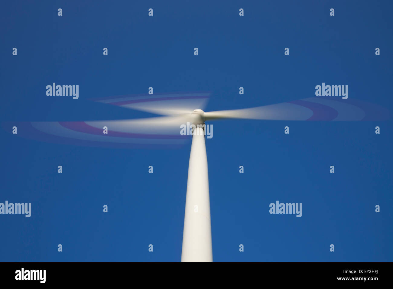 Worm's eye view on spinning rotor blades of wind turbine against blue sky - Stock Image