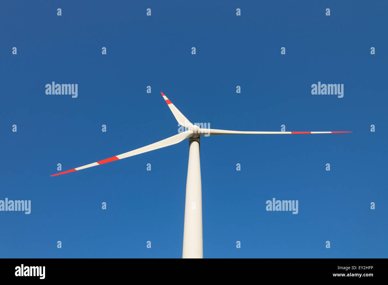 Worm's-eye view on rotor blades of wind turbine against blue sky - Stock Image