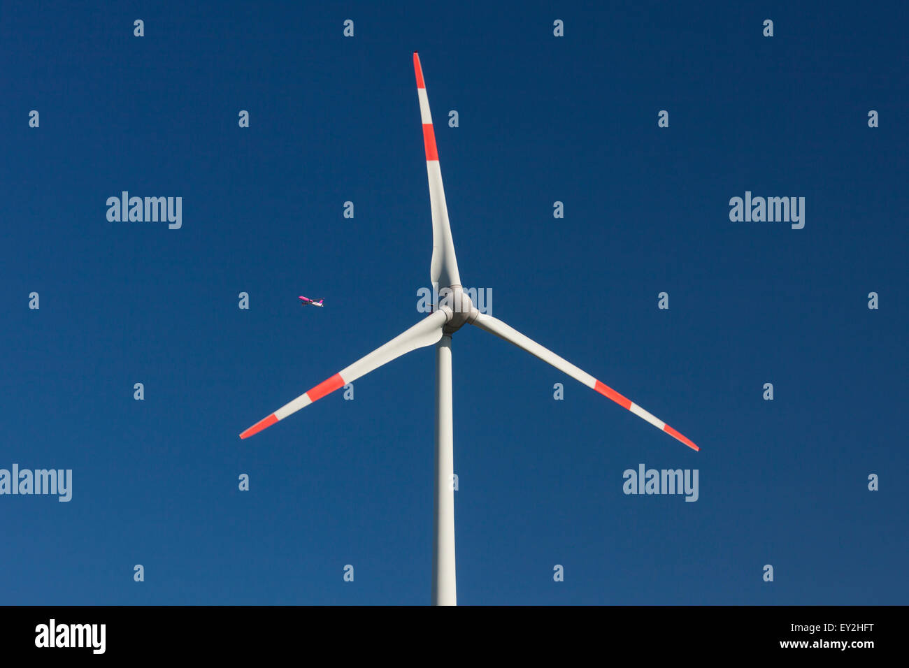 Jet airliner seen through rotor blades of wind turbine against blue sky - Stock Image