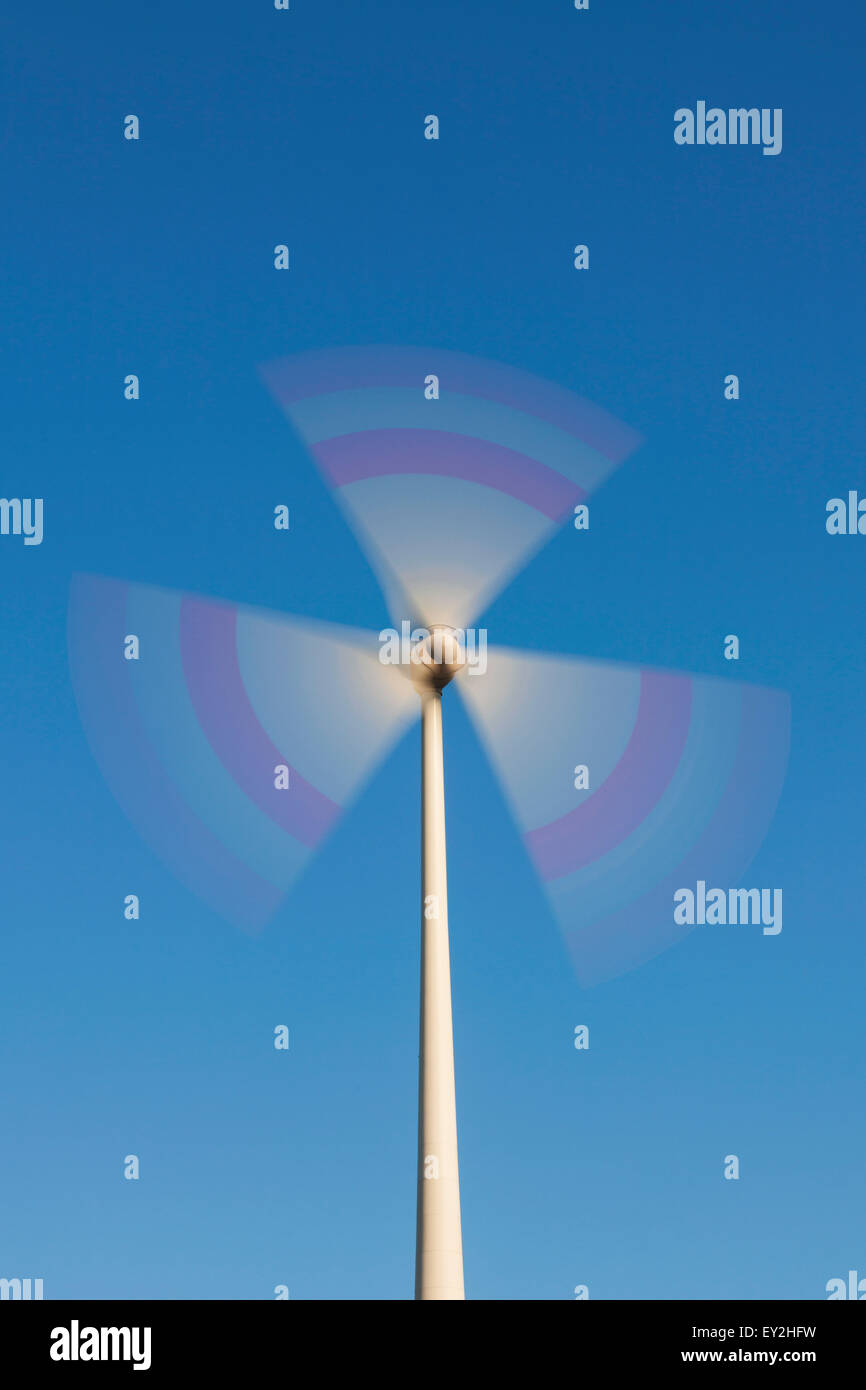 Spinning rotor blades of wind turbine against blue sky - Stock Image
