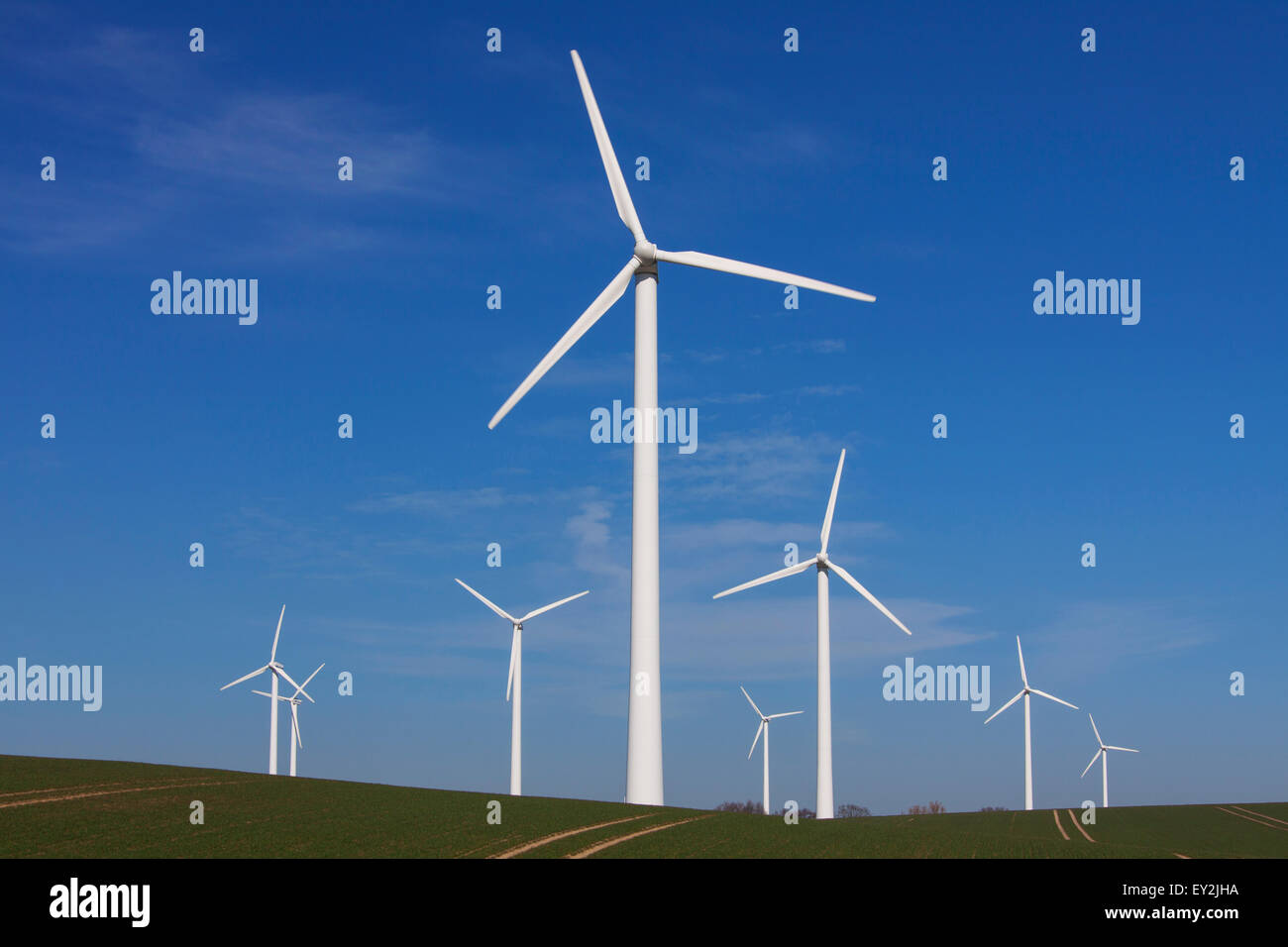Wind turbines at windfarm in field against blue sky - Stock Image