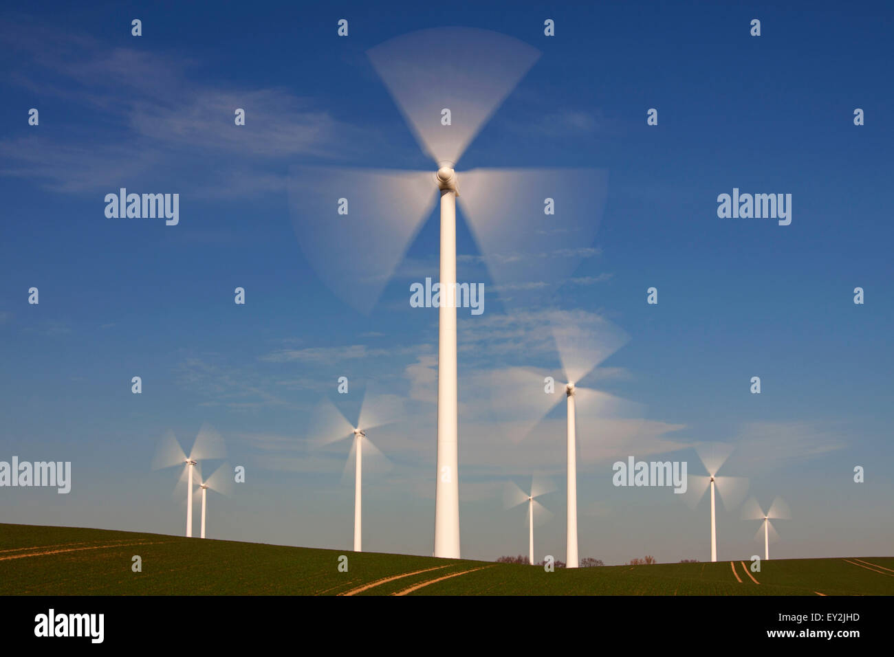 Spinning blades of wind turbines at windfarm against blue sky - Stock Image