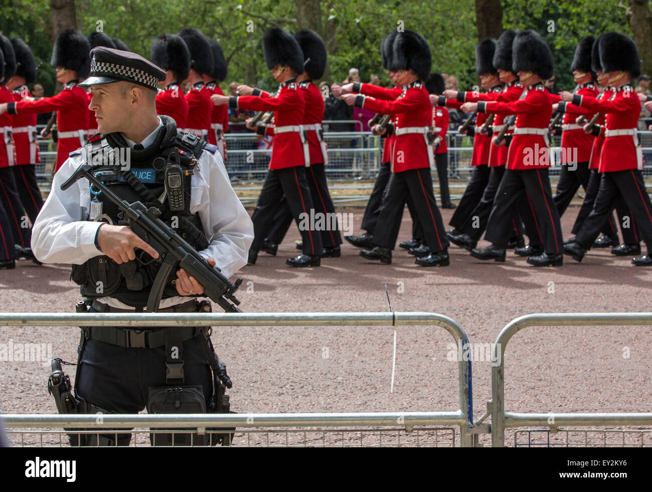 Heavily armed London policeman and Queen's Guard along the Trooping the Colour parade route on the Mall - Stock Image