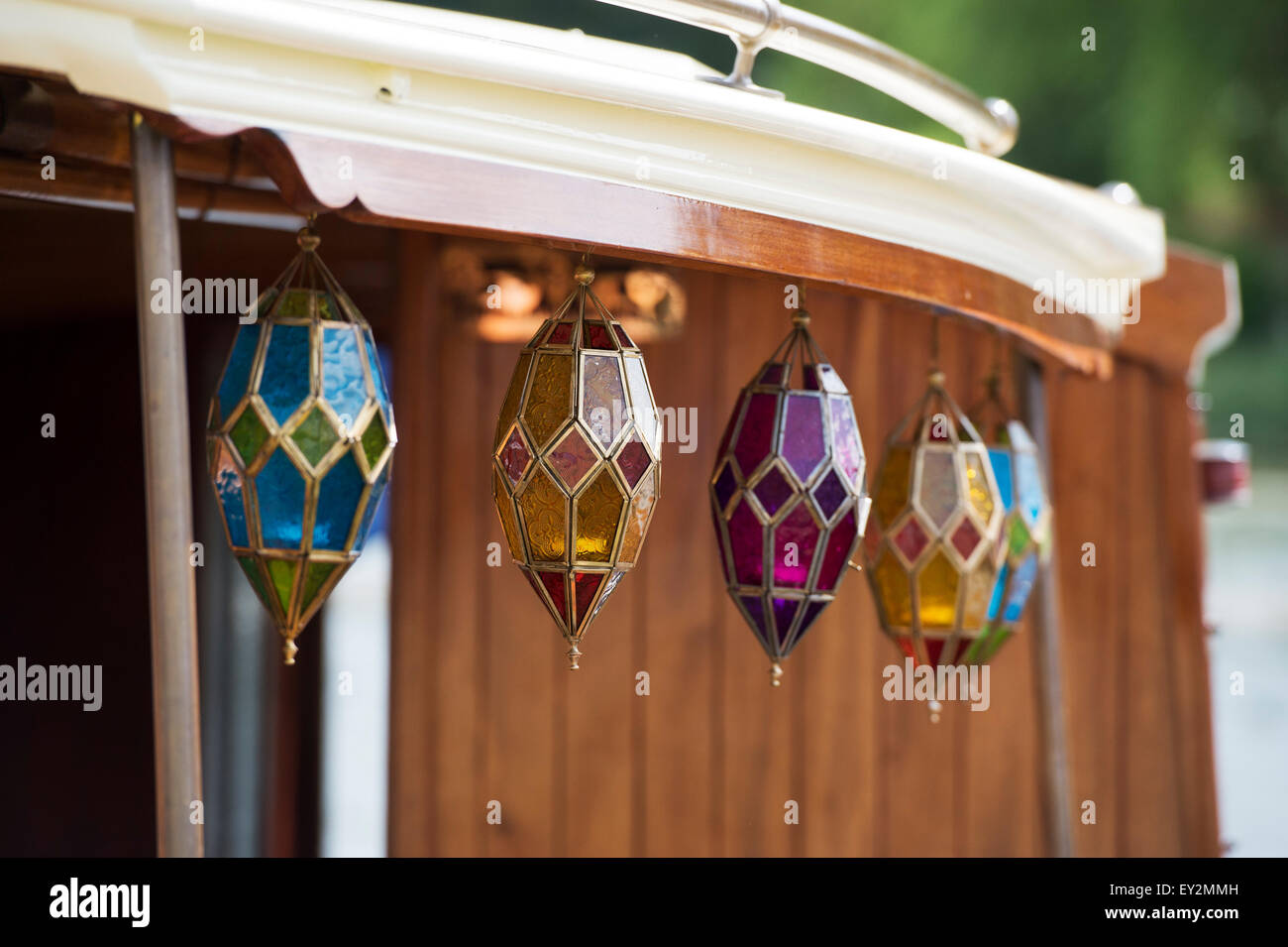 Colourful glass candle holders hanging on a wooden boat at the Thames Traditional Boat Festival, Henley On Thames, - Stock Image