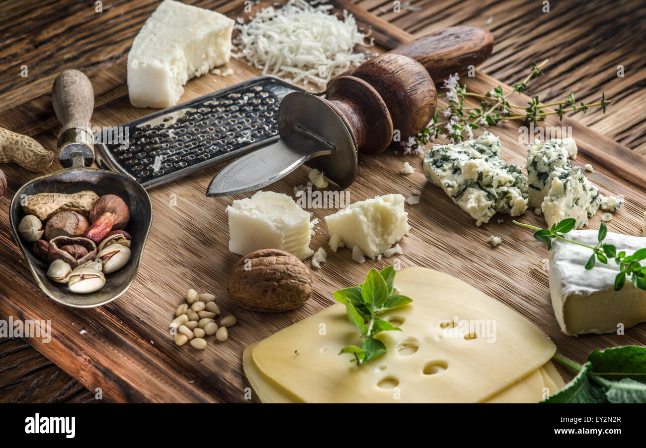 Different types of cheeses with nuts and herbs. Top view. - Stock Image