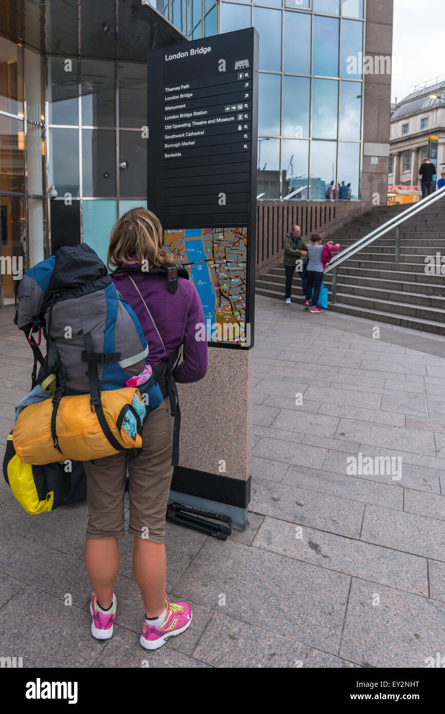 A backpacker looking for directions at a signpost at London Bridge - Stock Image