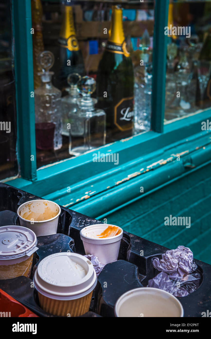 Empty cups and rubbish discarded next to a shop with a window display of champagne and cut glass creating a concept - Stock Image