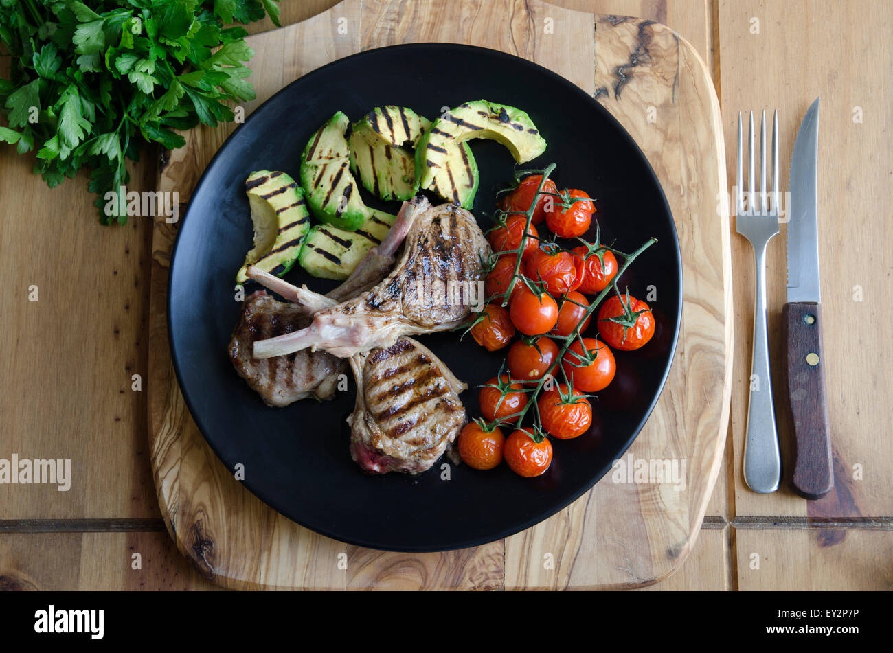 Lamb cutlets with avocado and tomatoes - Stock Image