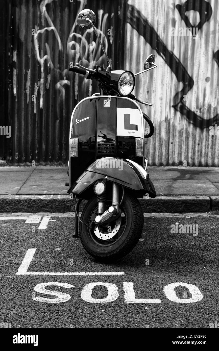 A Vespa scooter parked in a motorcycle bay with the word 'solo' marked on the road infront of it - Stock Image