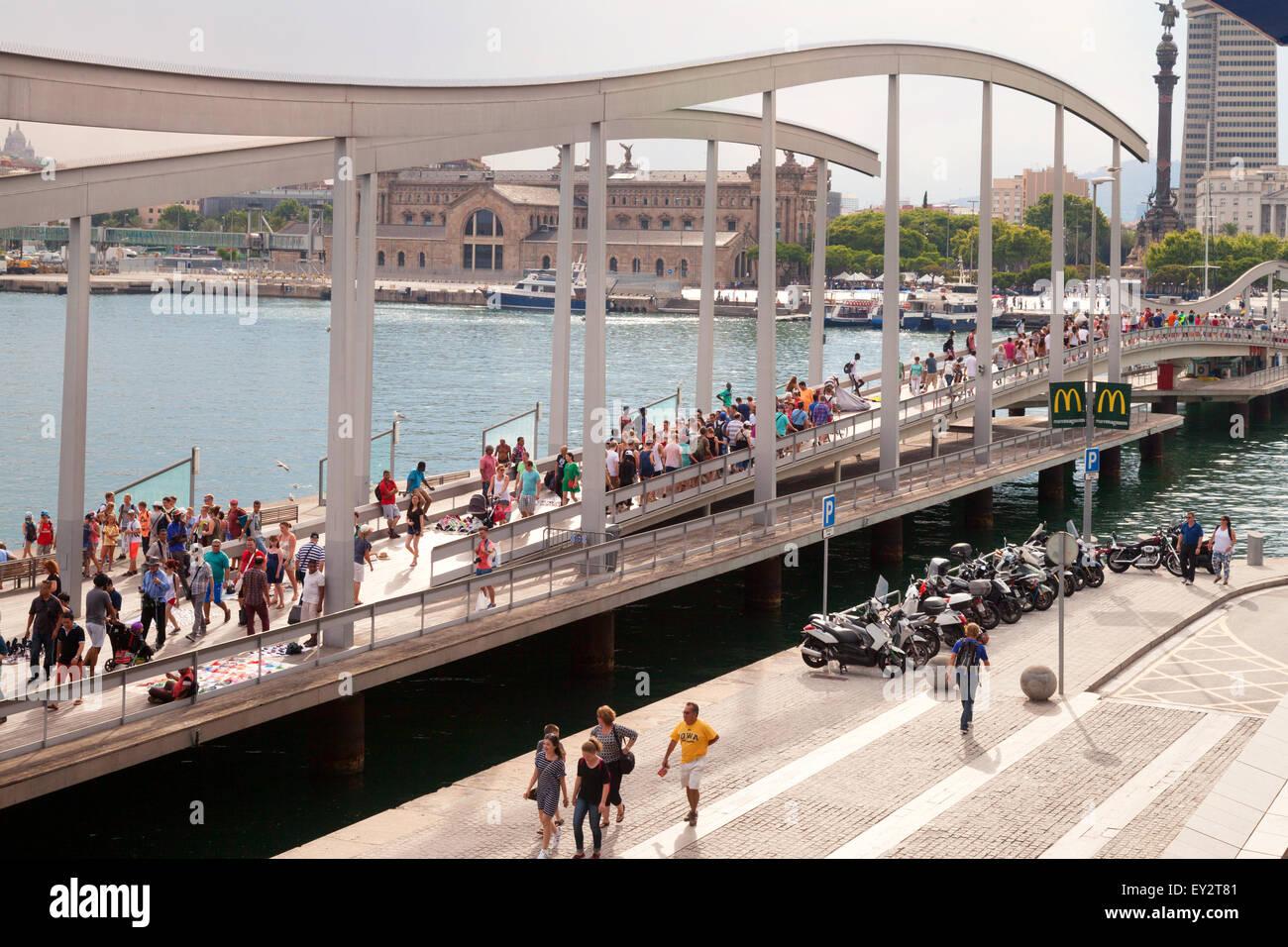 People crossing the bridge on the Rambla de Mar walkway, Port Vell, Barcelona, Spain Europe - Stock Image