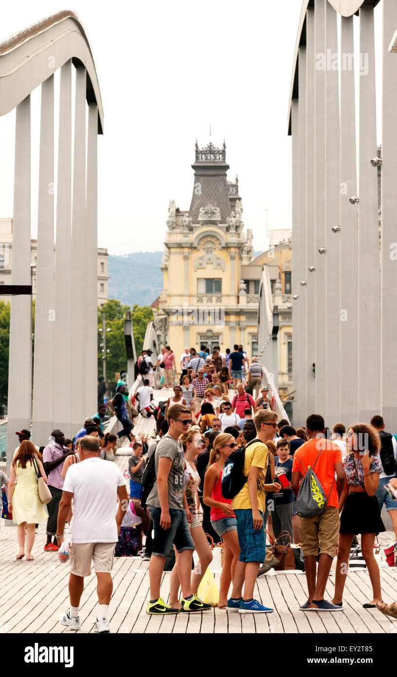 People crossing the bridge on the Rambla de Mar walkway, Port Vell, Barcelona Spain Europe - Stock Image