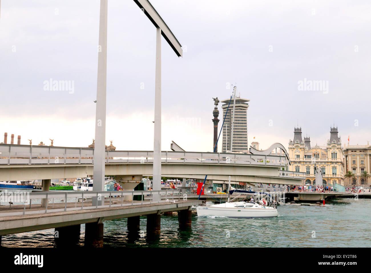 The swing bridge opening to allow a sailboat through, The Rambla de Mar walkway, Port Vell, Barcelona, Spain Europe - Stock Image