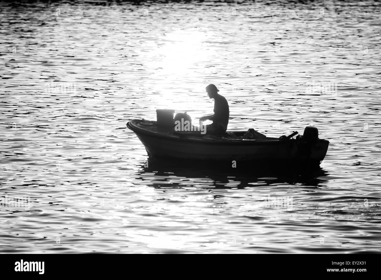 A fisherman in a motor boat fishing in the Adriatic sea at sunset on in Rovinj, Croatia. - Stock Image