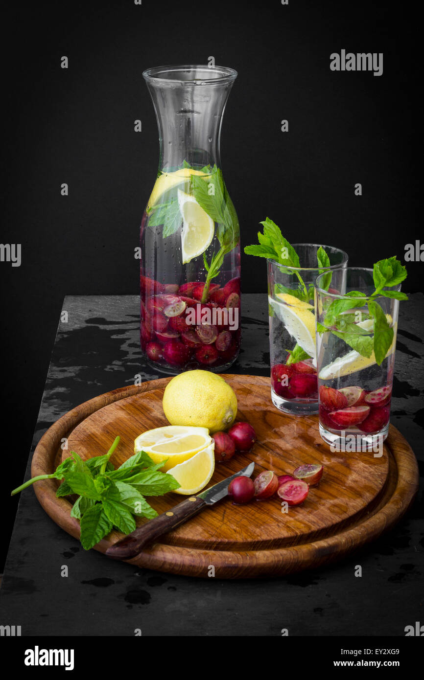 Water pitcher with fresh fruit and herbs on slate table with wooden board - Stock Image