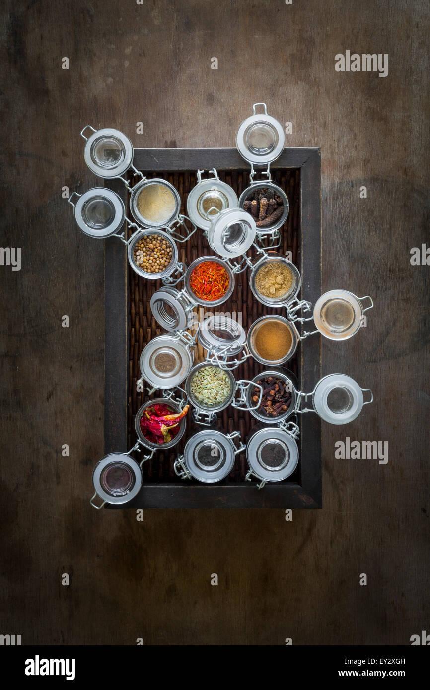 Spice jars in dark brown basket on dark wooden table. Top view Stock Photo