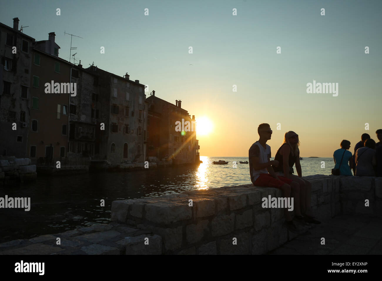 People sitting on the coast in front of the old city core buildings and watching the sunset in Rovinj, Croatia. - Stock Image
