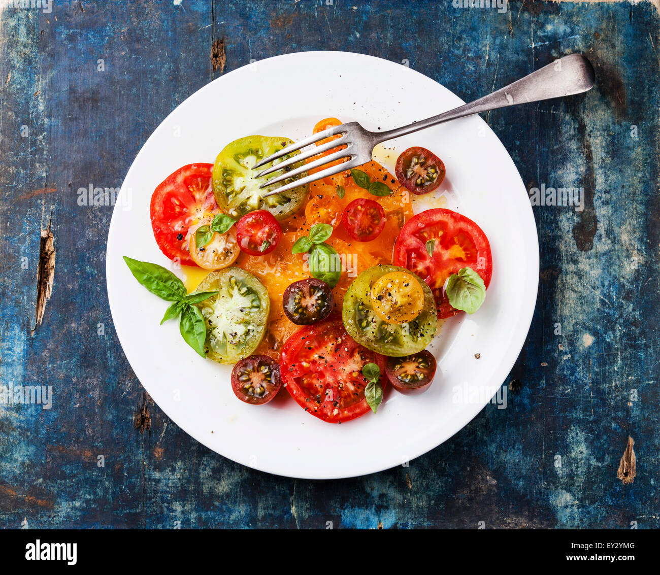 Ripe fresh colorful tomatoes salad with olive oil and basil on blue wooden background - Stock Image
