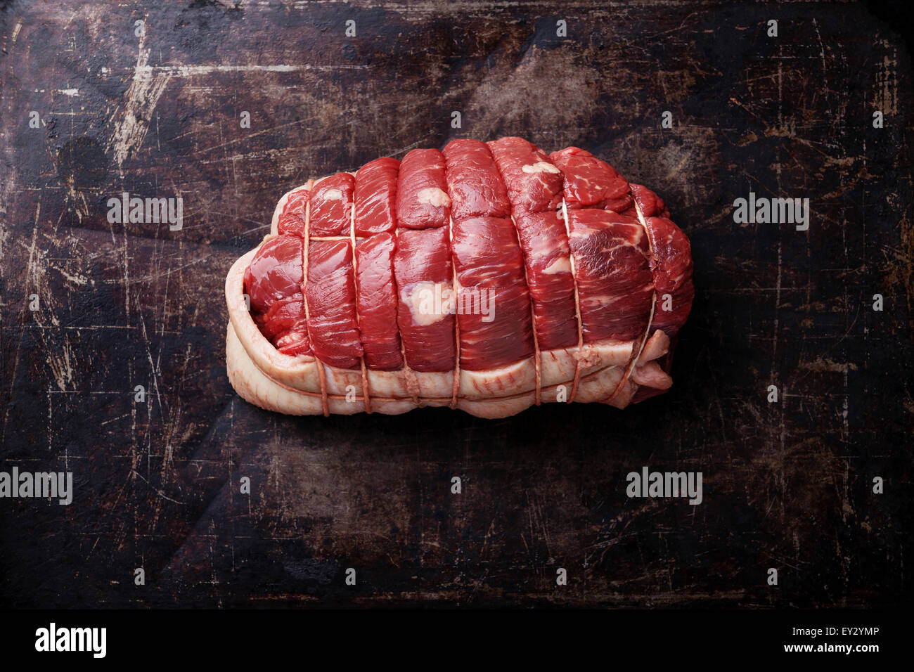 Rolled-up Roast beef meat on dark metal background - Stock Image
