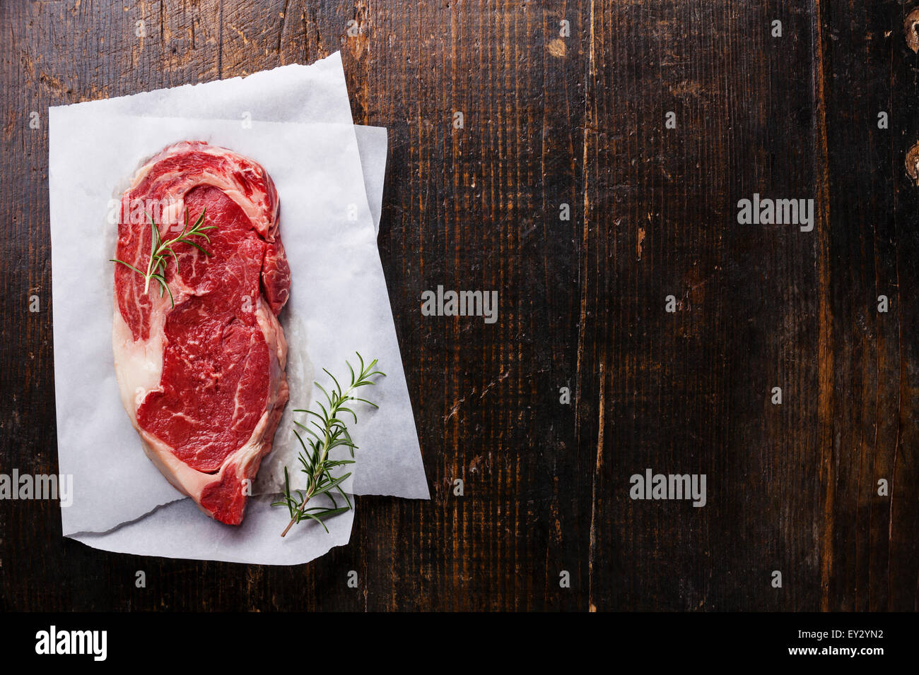 Raw fresh marbled meat Black Angus Steak and rosemary on dark wooden background - Stock Image