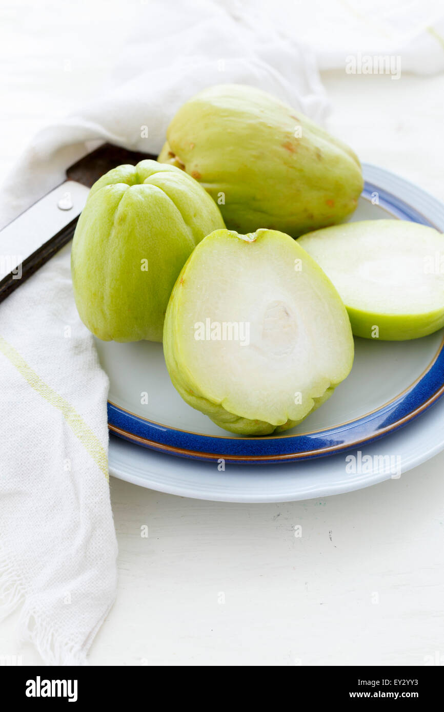 Chayotes on a plate, one of them sliced. - Stock Image