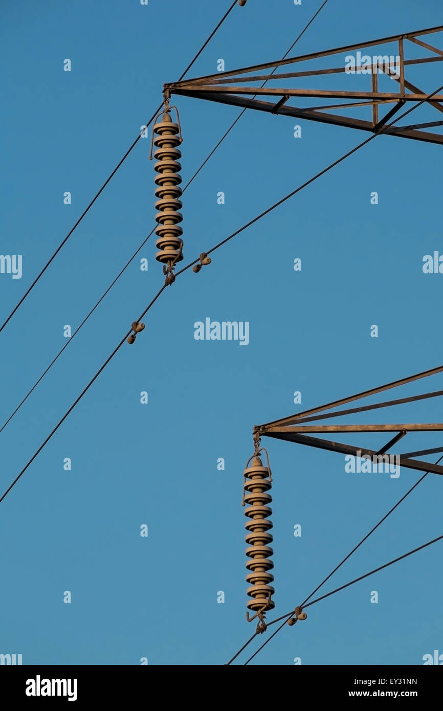 electricity pylon insulators and arms against a blue sky - Stock Image