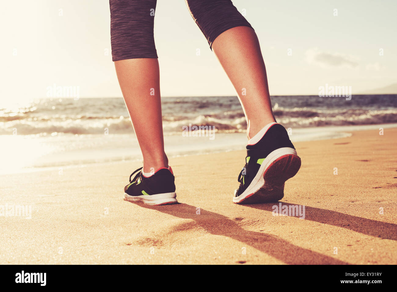 Close up of runner's feet at Sunset. Fitness woman, workout wellness lifestyle concept. - Stock Image