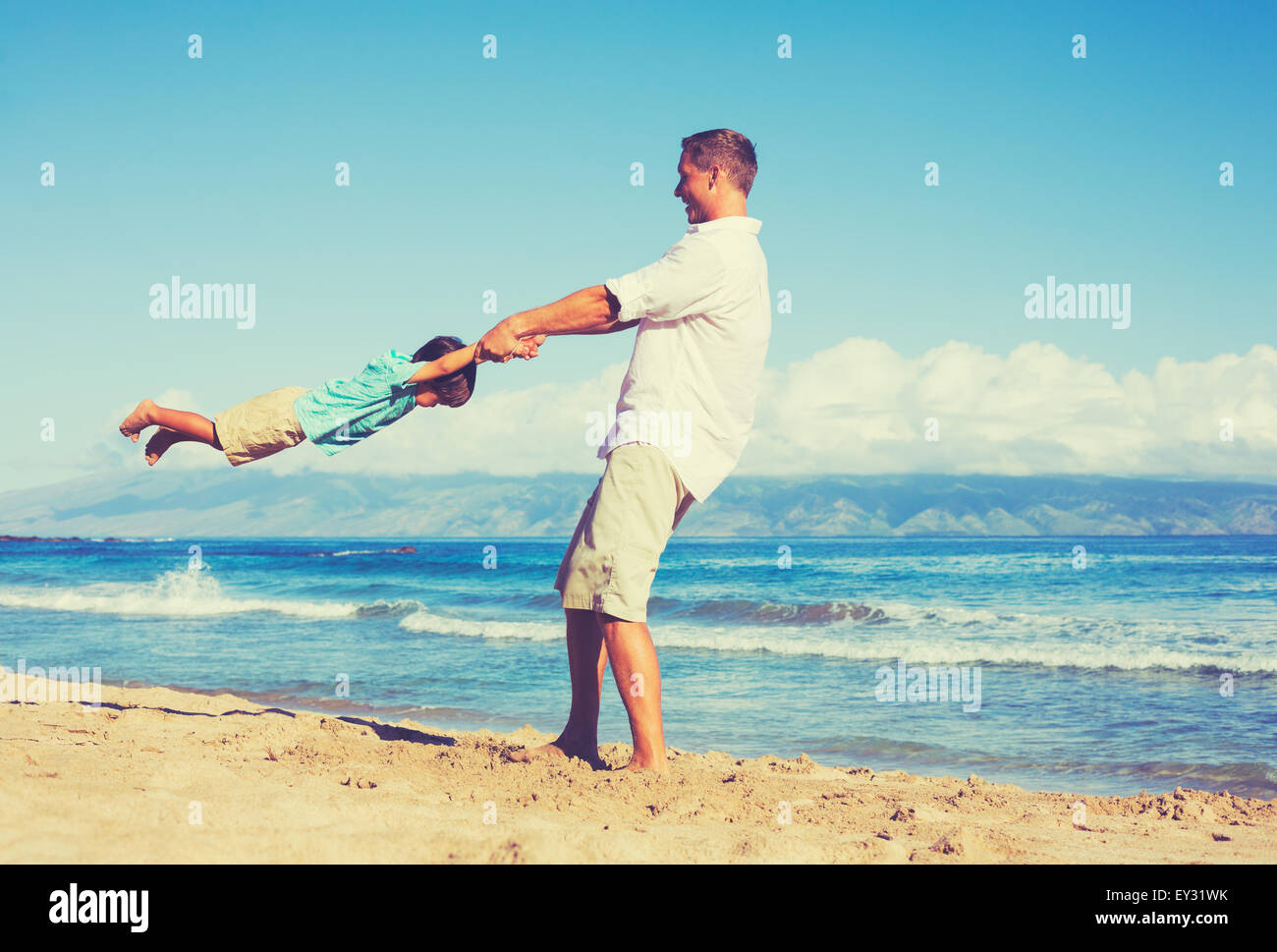 Happy father and son playing together at the beach. Fun vacation summer lifestyle. - Stock Image