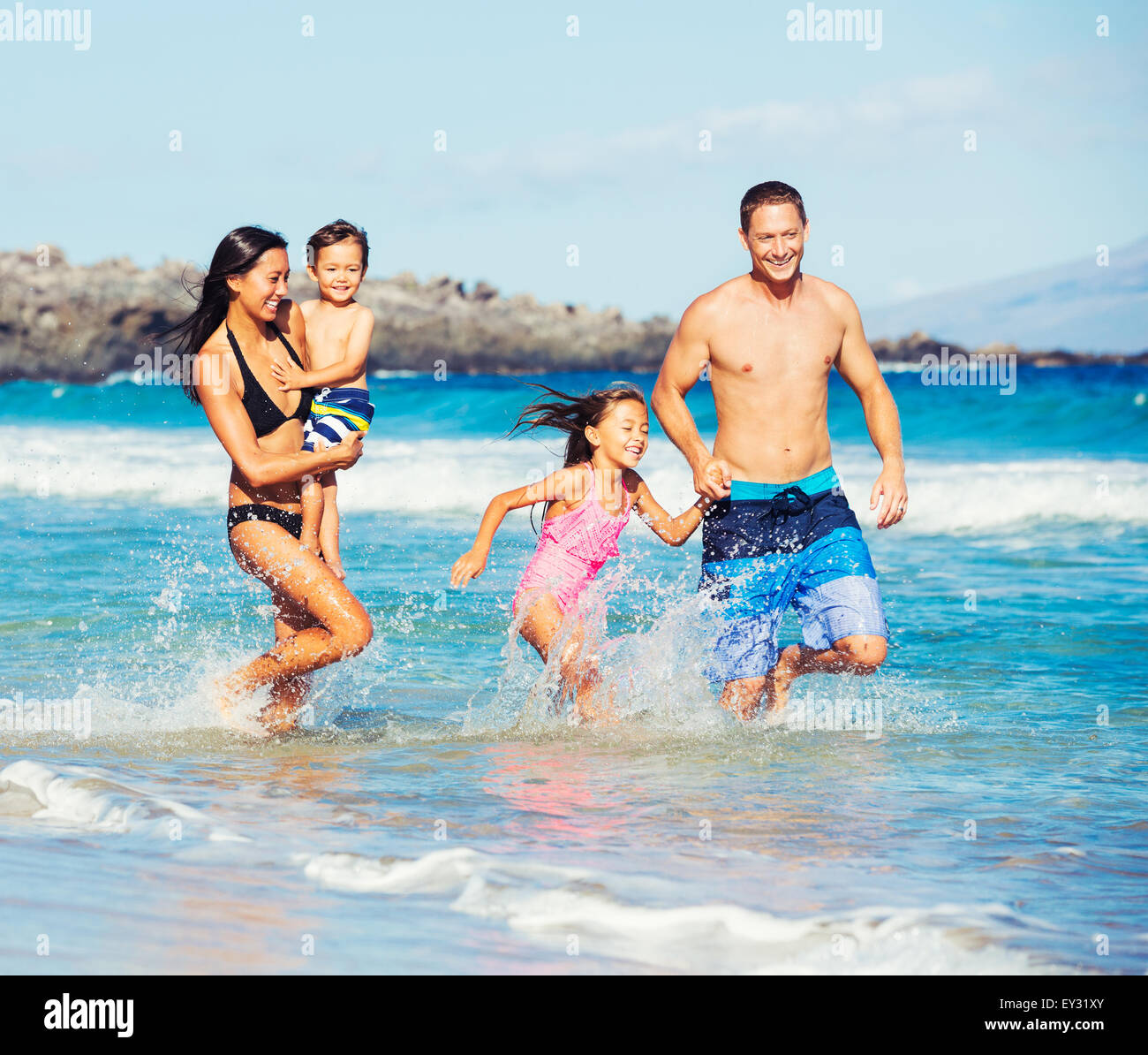 Young Happy Family Playing Having Fun at the Beach Outdoors - Stock Image