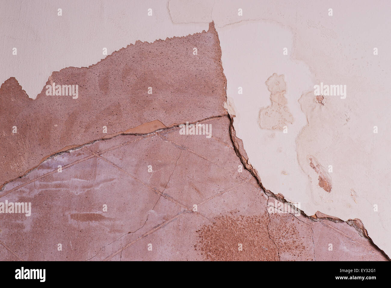 interior wall showing cracked and damaged plaster due to damp - Stock Image