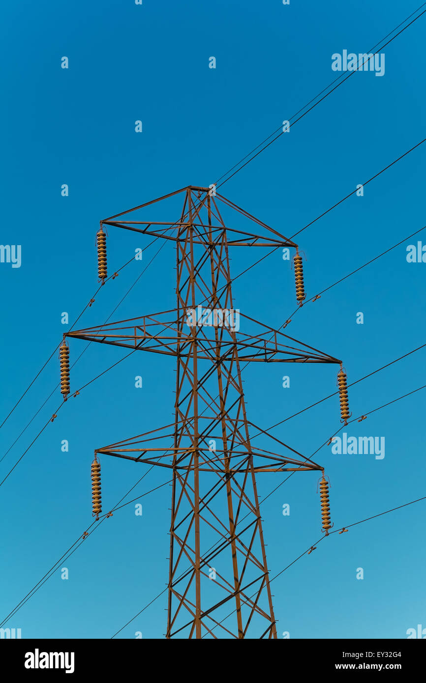 electricity pylon with six arms against a blue sky - Stock Image