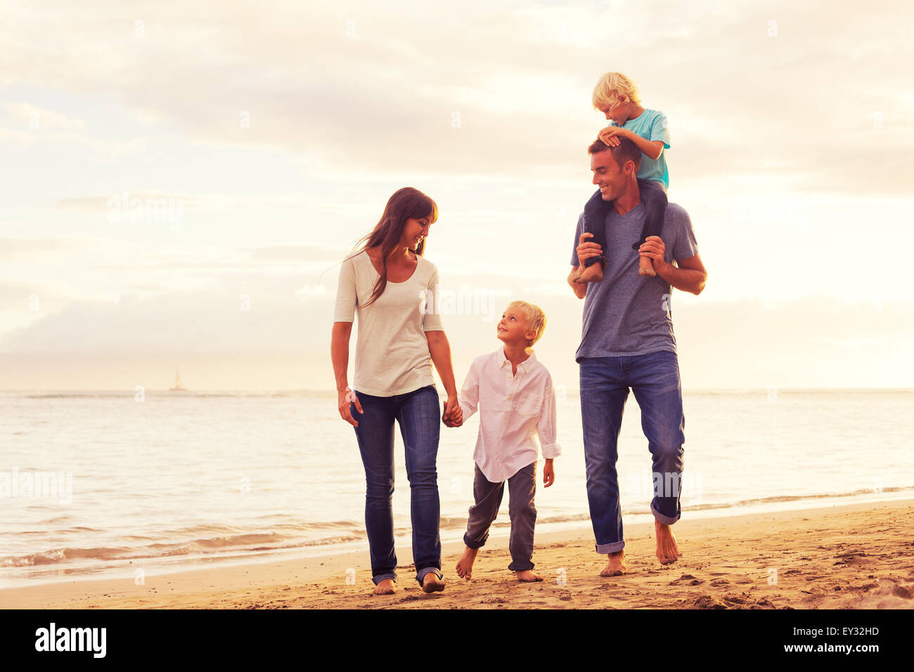 Happy young family having fun walking on the beach at sunset - Stock Image