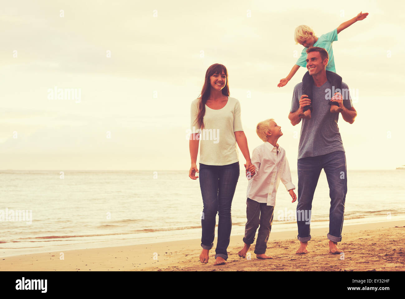 Happy young family on the beach at sunset - Stock Image