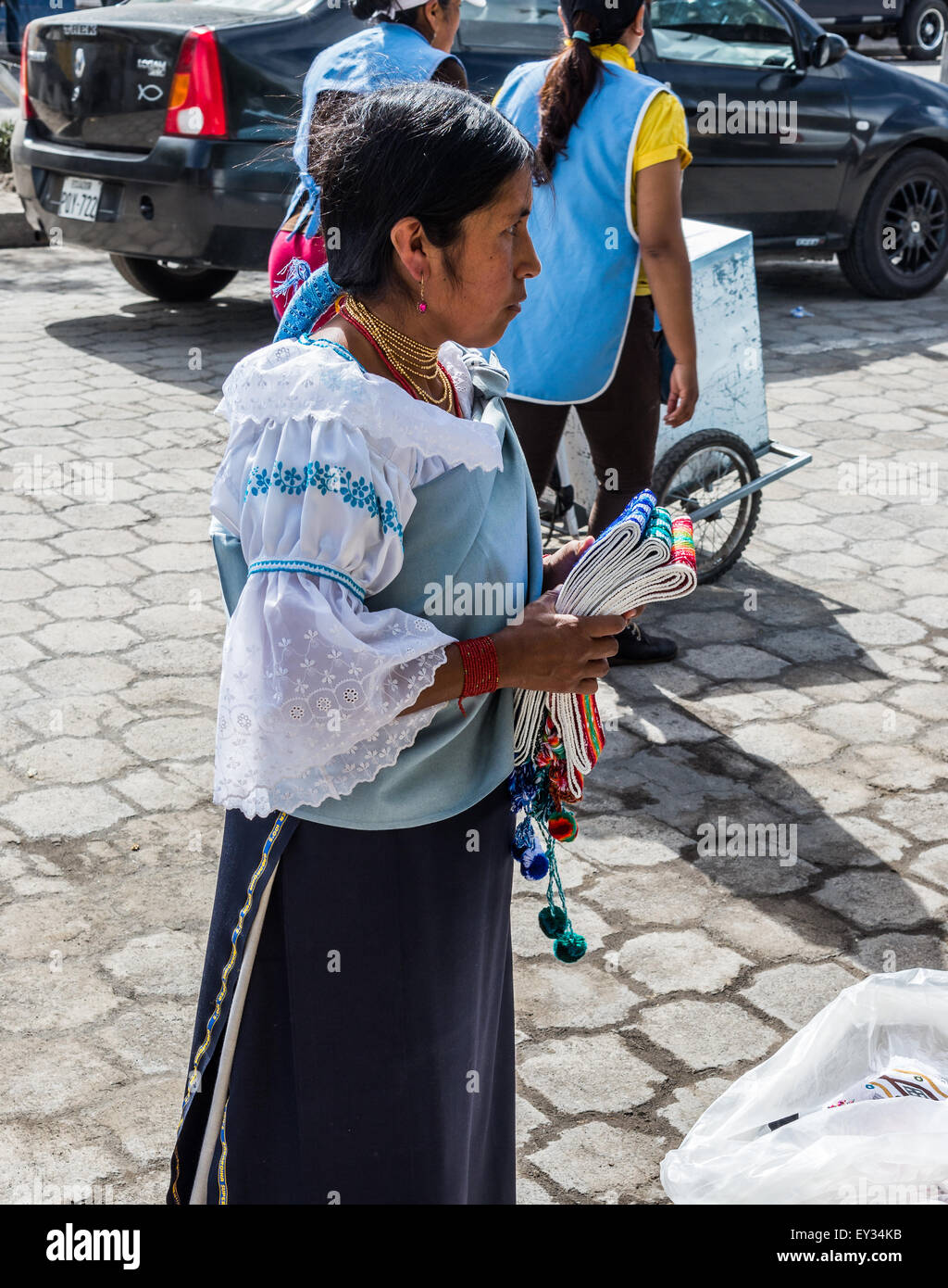 A young woman selling traditional embroiled belts at local market. Otavalo, Ecuador. - Stock Image