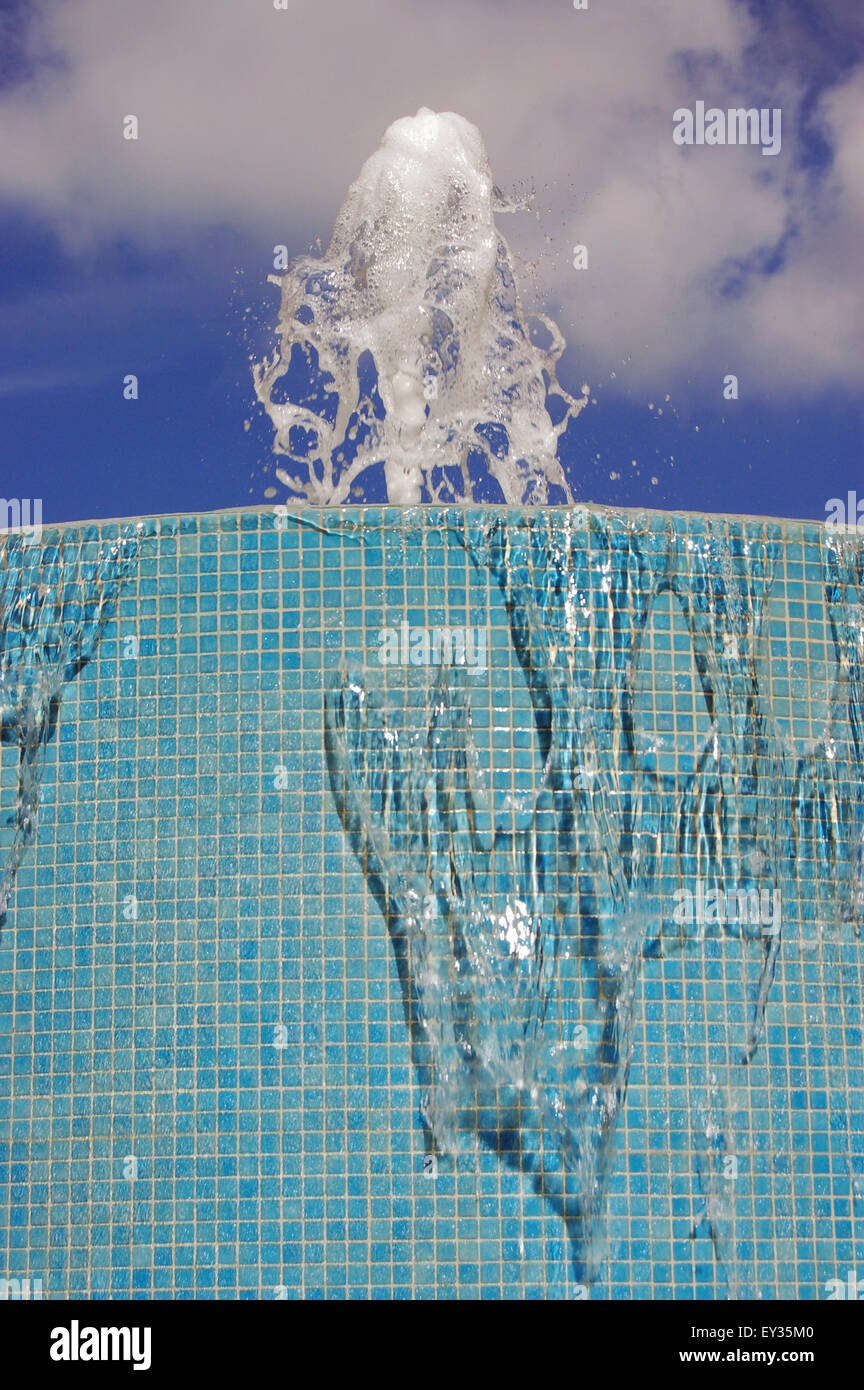 Close up view of a light blue tiled fountain with water spouting upwards against a sunny sky. - Stock Image
