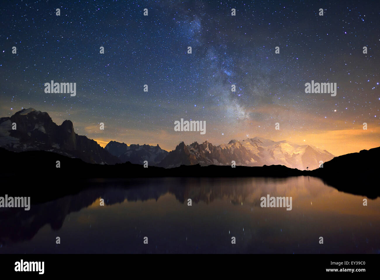 Mont Blanc massif at night with the Milky Way, reflected in Lac de Chésserys, Aiguilles de Chamonix on the - Stock Image
